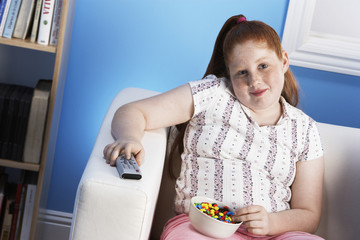 Overweight girl 13-15 Eating Junk Food, holding remote control
