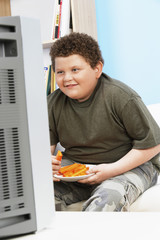 Overweight Boy 13-15 Eating Carrot Sticks in Front of Television