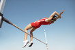 High Jumper in mid air over bar, view from below