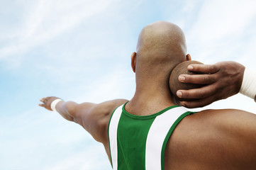 Shot Putter holding shot put, head and shoulders, back view