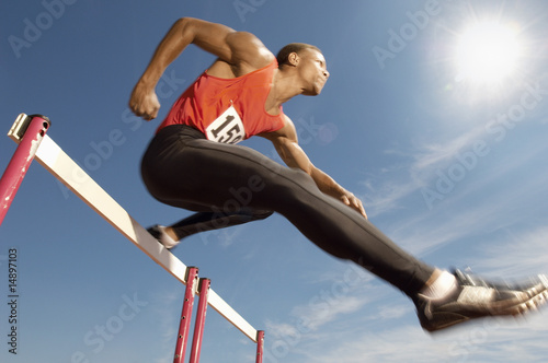 Male athlete jumping hurdle, mid air