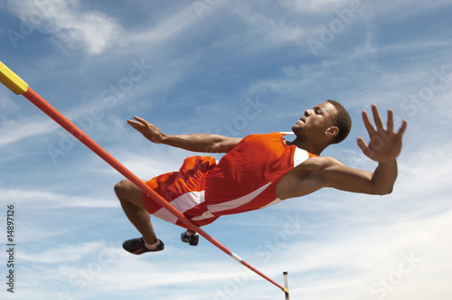 High Jumper in mid air over bar, low angle view