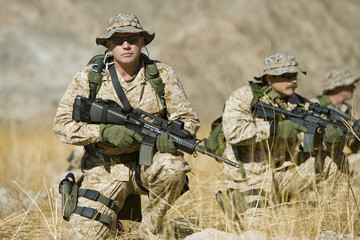 Soldiers with rifles in field