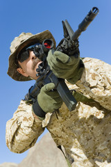 Soldier aiming rifle, outdoors, low angle view