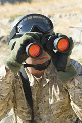 Soldier using binoculars, outdoors, close-up