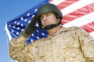 Soldier saluting in front of United States flag, portrait