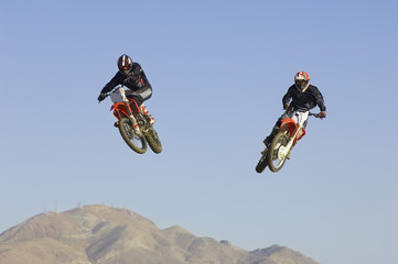 Two motocross Racers in mid-air