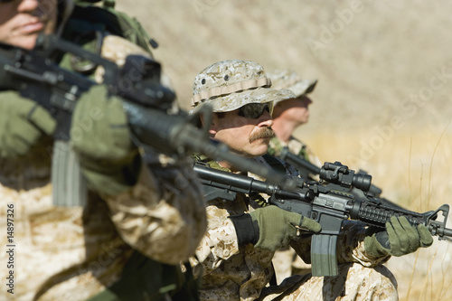 Soldiers aiming rifles in field
