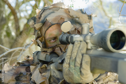Soldier aiming through gunsight, outdoors, close-up