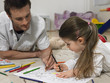 Father and daughter 3-4 colouring in book on floor
