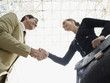 Businessman and businesswoman shaking hands, low angle view