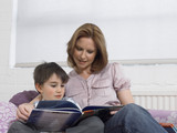 Mother and son 5-6 reading book on couch in living room