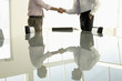 Businessmen shaking hands by conference table, mid section