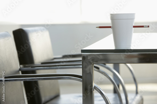Cup pierced by pencil on table in office