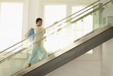 Woman walking up the modern stairs with shopping bags, portrait