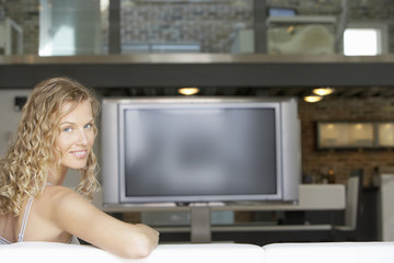 Woman sitting in modern living room, plasma television in background, portrait