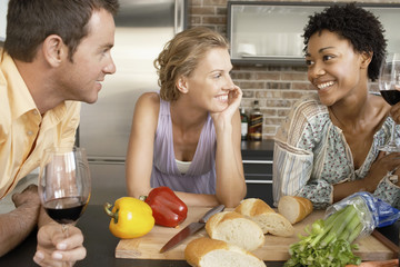 Friends talking while preparing dinner, portrait