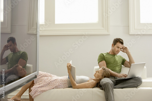 Couple relaxing together on sofa, man using laptop, woman reading
