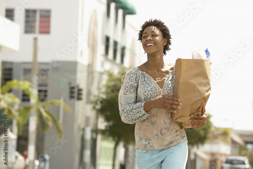 Smiling young woman carrying groceries, portrait