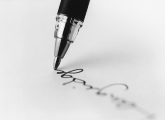 Tip of pen writing on paper, b&w, close-up