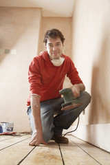 Man holding sanding tool,  in unrenovated room, portrait,