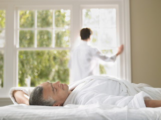 Man relaxing in bed, wife looking through window in background