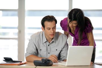 homme assis à un bureau lisant un document avec une femme