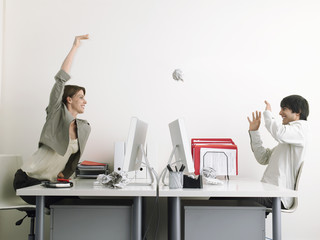 Woman throwing paper at man in office, side view