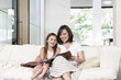 Mother and daughter reading book in living room, portrait