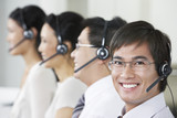 Row of customer service representatives wearing telephone headsets in office, head and shoulders