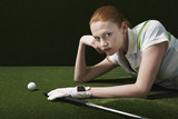 Woman reclining on floor with golf club and ball, portrait