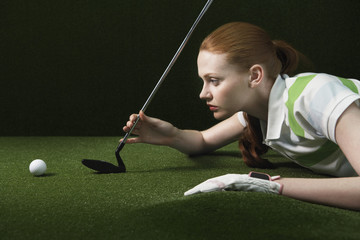 Woman reclining on floor, holding golf club, looking at golf ball
