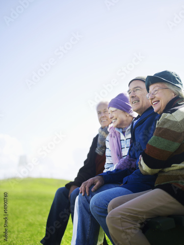 Four senior friends sitting outdoors, laughing
