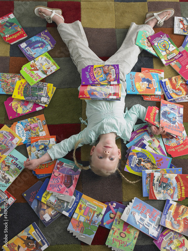 Girl lying on library floor with books scattered around, view from above