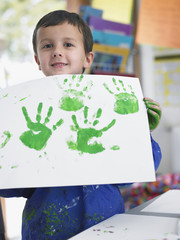Boy presenting his finger painting in art class