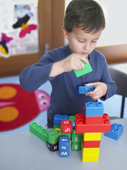 Boy playing with building blocks in classroom, elevated view