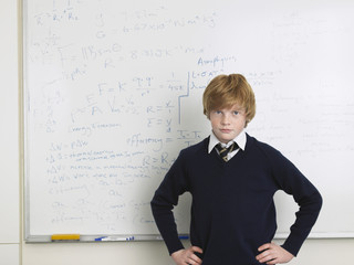 Elementary school student standing by whiteboard in math class, portrait