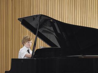 Pre teen boy playing piano in music class