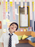 Elementary schoolboy looking up at paper strips with alphabet in classroom