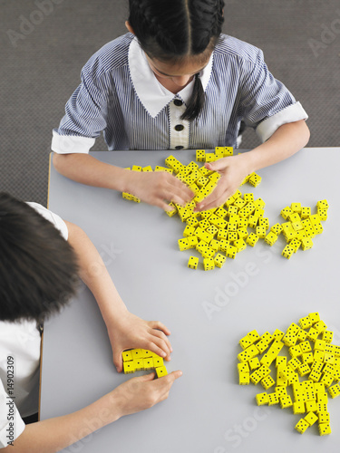 Elementary students playing with dice on desk, elevated view