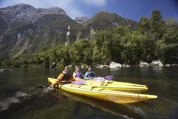 Three people paddling kayaks in mountain lake
