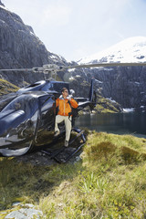 Hiker climbing out of helicopter on mountain top