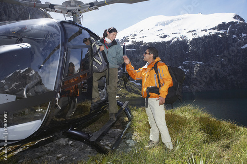 Hikers climbing out of helicopter on mountain peak