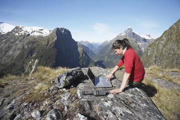Woman using laptop on mountain peak