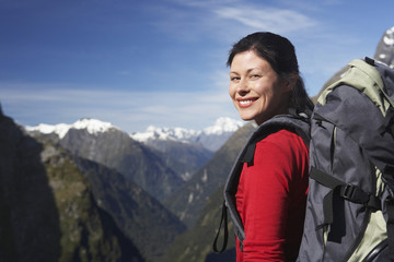 Female hiker wearing backpack on mountain peak