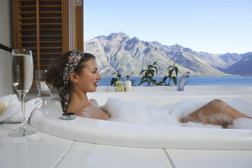 Woman taking a bubble bath with champagne with mountain lake outside window