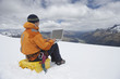 Hiker using laptop on snowy mountain peak, back view