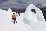 Two hikers going past ice formation in mountains, back view
