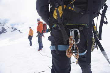 Hiker's back with backpack and safety rope in snowy mountains with two friends ahead, back view