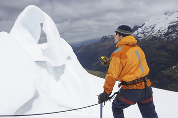 Mountain climber holding compass near ice formation in snowy mountains